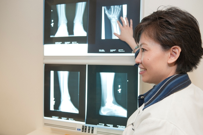 A rheumatologist discussing an X-Ray image, symbolizing the patient-doctor relationship necessary for positive outcomes
