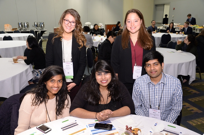 Four rheumatology students smiling at a table during the Foundation student and resident experience