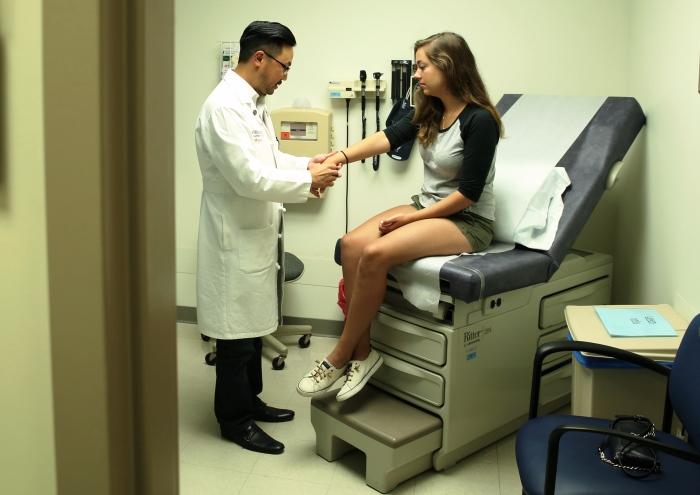 Dr. Al Kim examines a patient with juvenile arthritis.