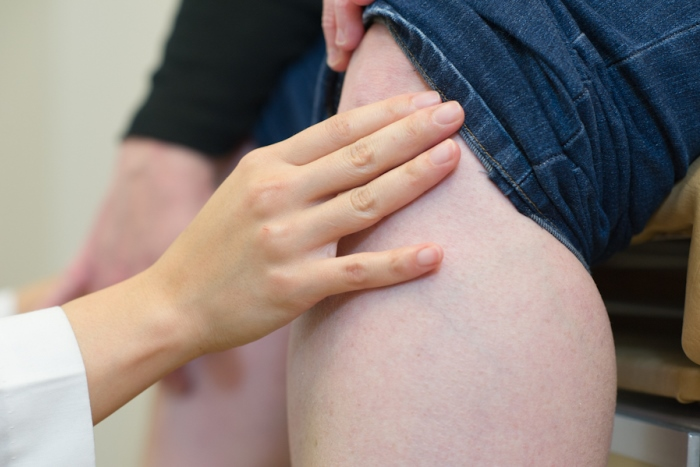 A rheumatologist examines a patient who has osteoarthritis in the knee.
