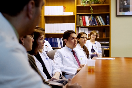 Rheumatology researchers gather around a table.